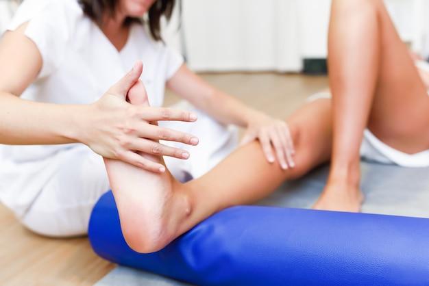 Medizinische kontrolle an den beinen in einem physiotherapie-zentrum. Kostenlose Fotos