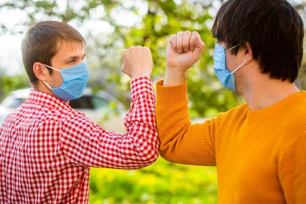Medizinische maske der freunde. ellbogen stoßen. Premium Fotos