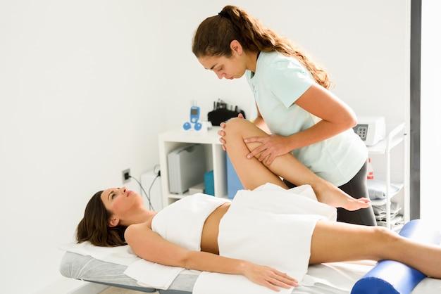 Medizinische massage am bein in einer physiotherapie-mitte. Kostenlose Fotos