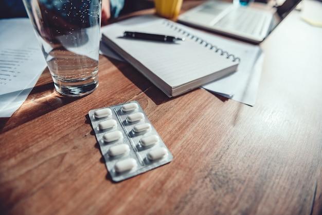 Medizinische pillen und glas wasser am schreibtisch Premium Fotos