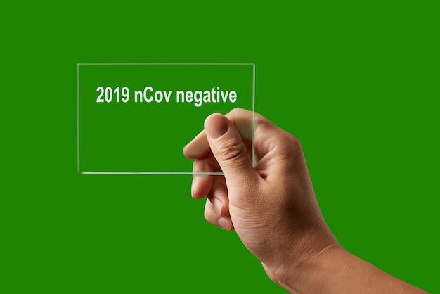 Medizinischer test mit menschlicher hand und negatives ergebnis für 2019 ncov gegen einen grünen backplatz, kopierraum. ausbruch von coronavirus, covid-19 oder pandemiekonzept. Premium Fotos