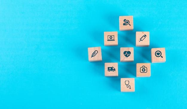 Medizinisches kontrollkonzept mit holzklötzen mit ikonen auf blauem tisch flach legen. Kostenlose Fotos