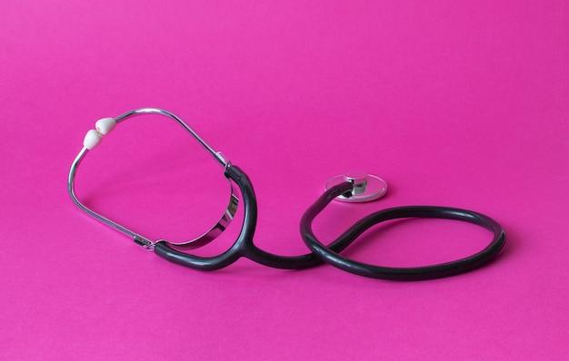 Medizinisches stethoskop auf rosa hintergrund. gesundheits- und kardiologie-hintergrund Premium Fotos