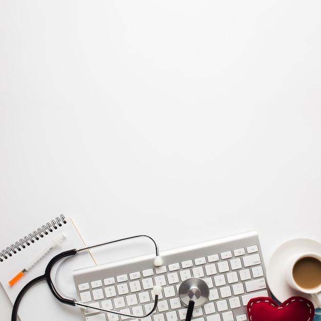 Medizinisches werkzeug und tasse kaffee mit dem genähten spielzeugherzen lokalisiert auf weißem hintergrund Kostenlose Fotos