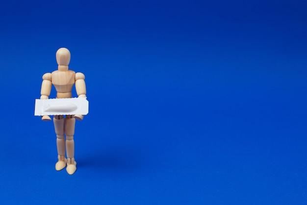 Medizinisches zäpfchen, rektal oder vaginal. hölzerner mann hält medizinisches zäpfchen auf blauem hintergrund. Premium Fotos
