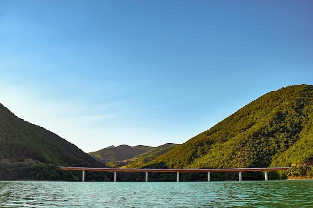 Meer mit einer betonbrücke, umgeben von hügeln, die unter dem sonnenlicht mit wäldern bedeckt sind Kostenlose Fotos