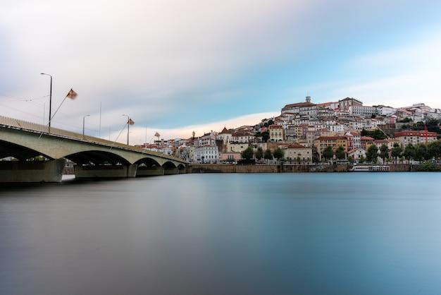 Meer mit einer brücke darauf, umgeben von der stadt coimbra unter einem bewölkten himmel in portugal Kostenlose Fotos