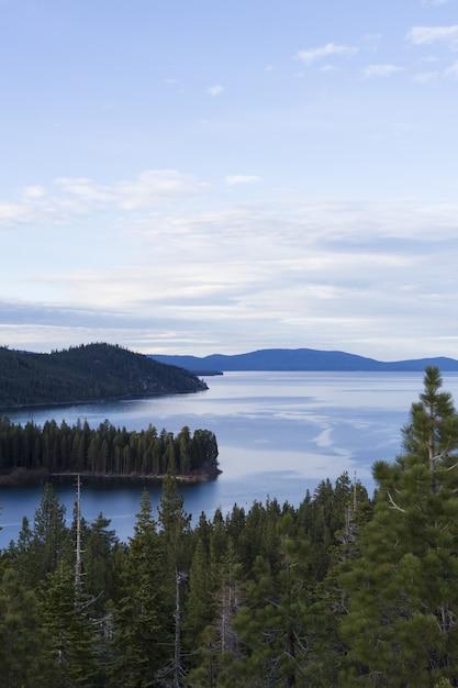 Meer umgeben von bewaldeten bergen unter einem blauen himmel Kostenlose Fotos