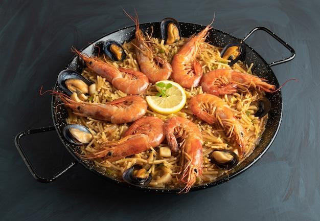 Meeresfrüchte-nudeln auf rustikalem holztisch - fideua Premium Fotos
