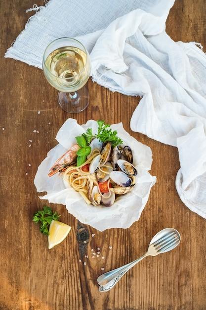 Meeresfrüchte pasta. spaghettis mit muscheln und garnelen in der schüssel, glas weißwein über rustikaler hölzerner tabelle Premium Fotos