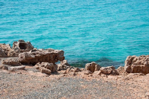 Meeresufer mit felsen und klarem transparentem meerwasser. natürlicher meereshintergrund. blaue ozean-tapete, meereswelle am sonnentag. kristallklares wasser und orangefarbene klippen des tropischen meeres Premium Fotos