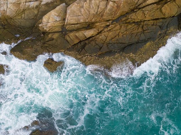 Meereswellen, die gegen die klippe angesehen von oben brechen Premium Fotos