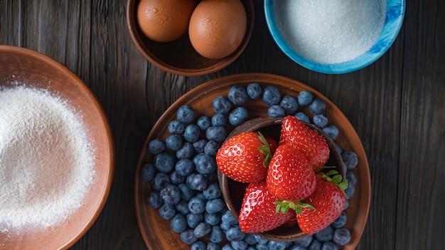Mehl, eier, zucker, eier und frische beeren sind die zutaten für einen köstlichen kuchen. heidelbeerkuchen Premium Fotos