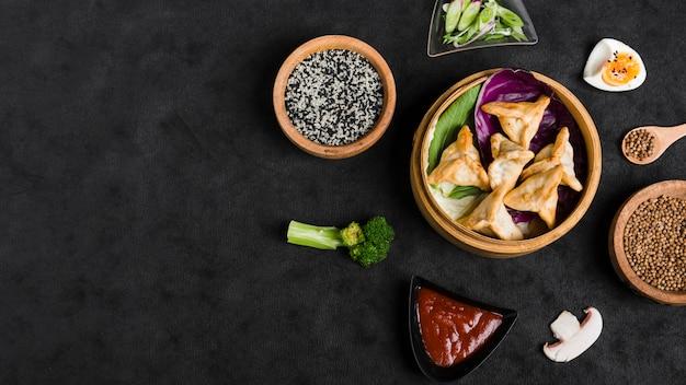 Mehlkloß in den dampfern umgeben mit bestandteilen auf schwarzem strukturiertem hintergrund Premium Fotos