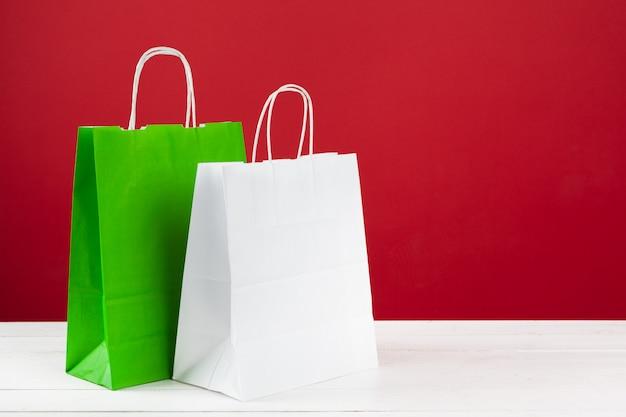 Mehrere einkaufstaschen mit kopienraum auf rotem hintergrund Premium Fotos