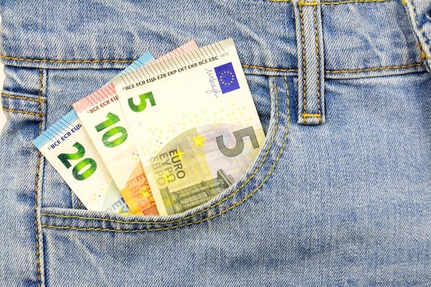 Mehrere euro-scheine werden in die jeans-tasche gesteckt Premium Fotos