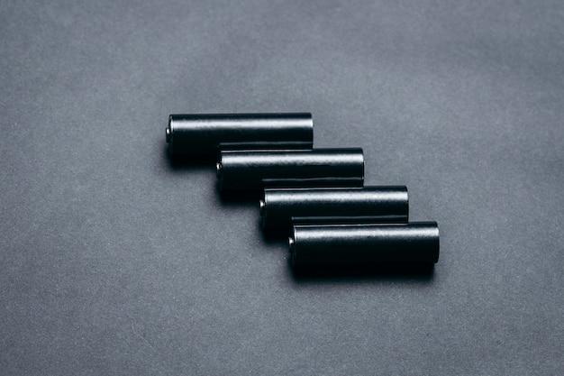 Mehrere leere aa-batterien auf schwarzem papier Premium Fotos