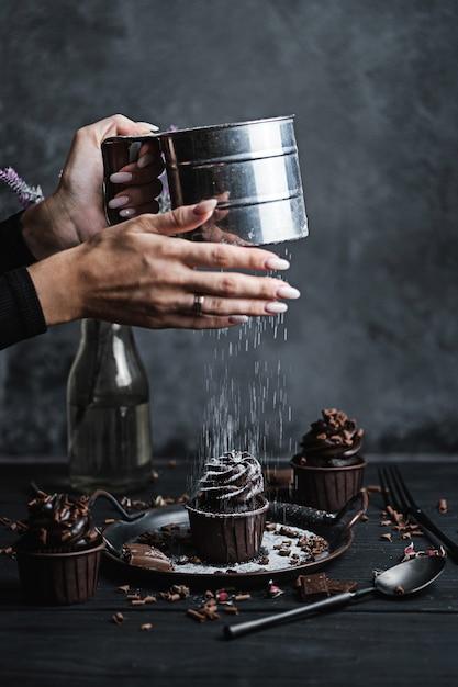 Mehrere muffins oder cupcakes mit schokoladenförmiger sahne am schwarzen tisch. die hand einer frau zerbröckelt puderzucker auf einem kuchen. Premium Fotos