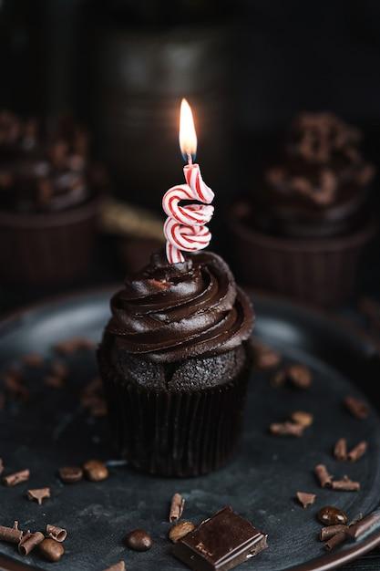 Mehrere muffins oder cupcakes mit schokoladenförmiger sahne am schwarzen tisch. festliche kerze brennt auf einem schokoladenkuchen Premium Fotos