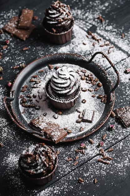 Mehrere muffins oder cupcakes mit schokoladenförmiger sahne am schwarzen tisch. puderzucker wird über die kuchen verteilt. Premium Fotos