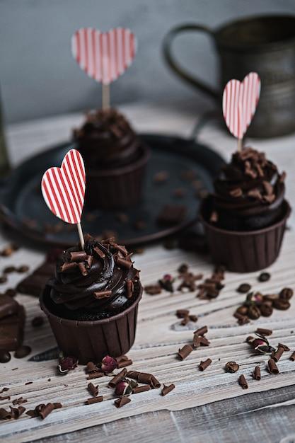 Mehrere muffins oder cupcakes mit schokoladenförmiger sahne am weißen tisch. eine weihnachtskarte in form eines herzens zum valentinstag in einem von ihnen. Premium Fotos