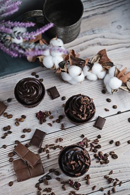 Mehrere muffins oder cupcakes mit schokoladenförmiger sahne am weißen tisch. Premium Fotos