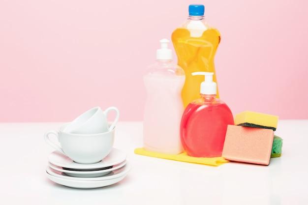 Mehrere teller, ein küchenschwamm und eine plastikflasche mit natürlicher spülmittelseife werden zum handgeschirrspülen verwendet. Kostenlose Fotos