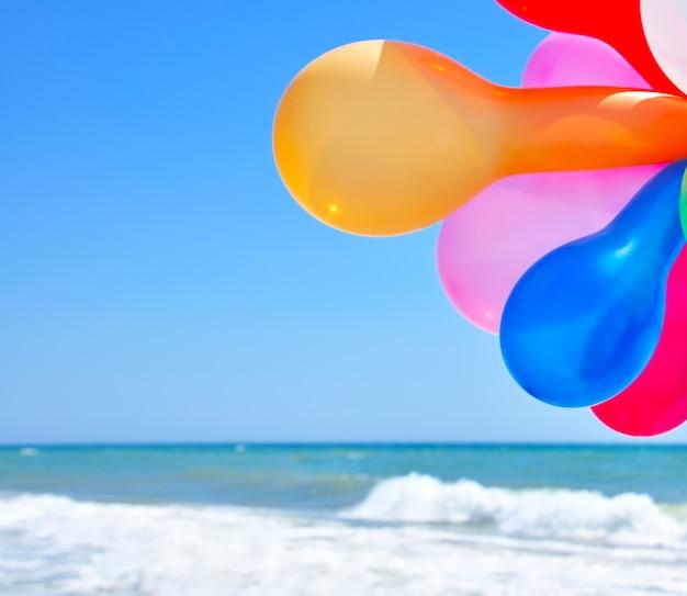 Mehrfarbige ballone gegen das meer Premium Fotos