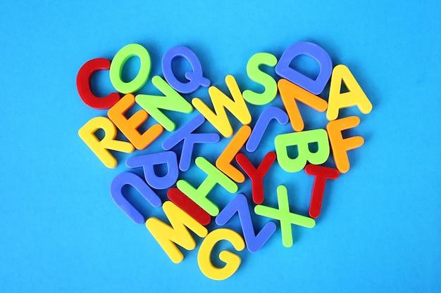 Mehrfarbige buchstaben des englischen alphabets werden in form eines herzens auf einen blauen hintergrund gelegt. Premium Fotos