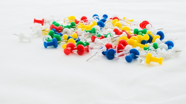 Mehrfarbige büro thumbtacks auf weiß Premium Fotos