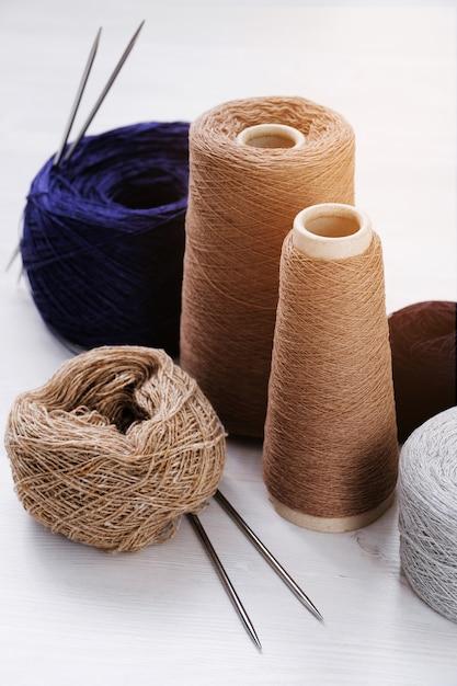 Mehrfarbige fäden, stränge und verwicklungen aus italienischem wollgarn, stricknadeln. das konzept des strickens, handarbeit, handgemacht. Premium Fotos