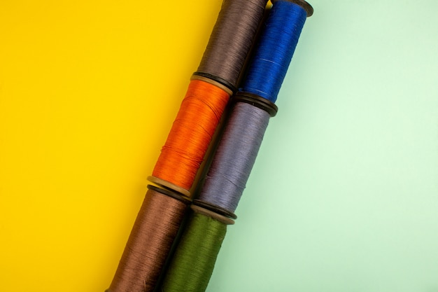 Mehrfarbige fäden zum nähen auf einem gelbgrünen boden Kostenlose Fotos