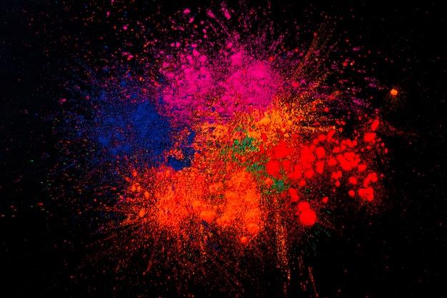 Mehrfarbige holi farben gemischt über schwarzem hintergrund Kostenlose Fotos