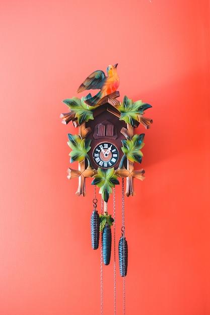 Mehrfarbige kuckucksuhr an roter wand Kostenlose Fotos
