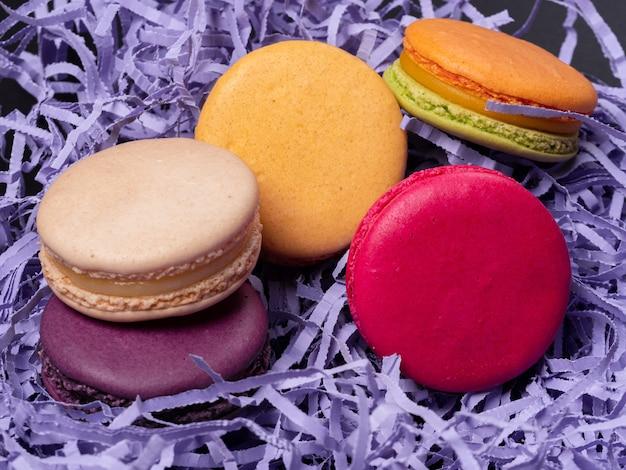 Mehrfarbige makronen auf einem lila tisch Premium Fotos