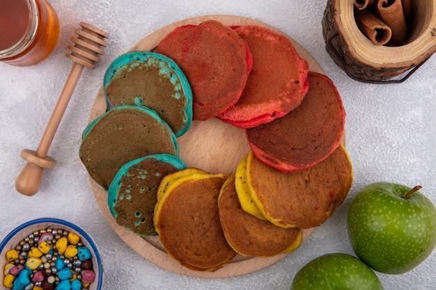 Mehrfarbige pfannkuchen der draufsicht auf einem stand mit grünen äpfeln farbigen pralinen zimt und honig auf einem weißen hintergrund Kostenlose Fotos