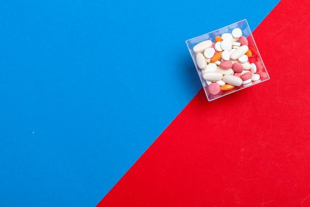 Mehrfarbige pillen auf blauem und rotem hintergrund. medizinisches konzept. Premium Fotos