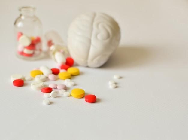 Mehrfarbige pillen und ein modell des menschlichen gehirns in der gefangenschaft. Premium Fotos