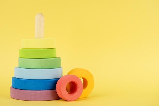 Mehrfarbige pyramide des babys auf gelbem hintergrund, kinderbildung Premium Fotos