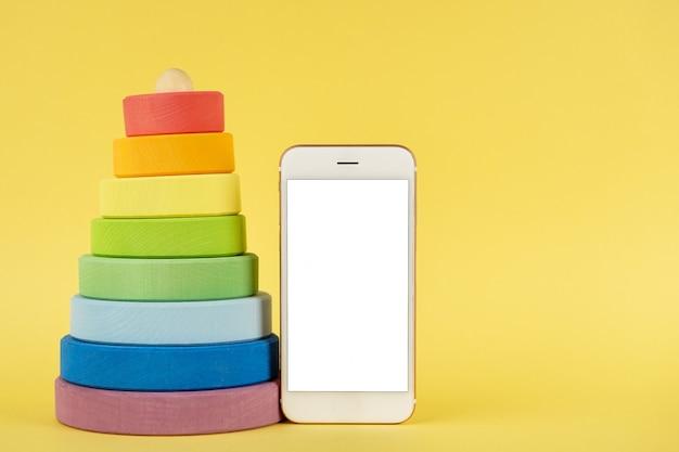 Mehrfarbige pyramide und handy des babys verspotten oben auf gelbem hintergrund Premium Fotos