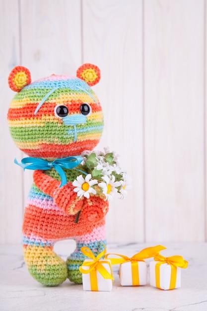 Mehrfarbiger gestrickter bär mit geschenken und blumen. gestricktes spielzeug, amigurumi, kreativität, diy Premium Fotos