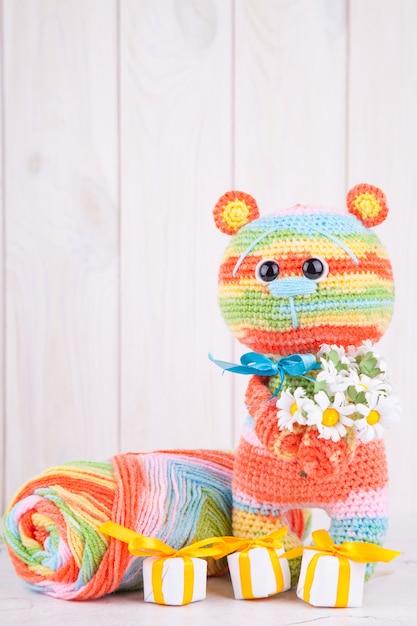 Mehrfarbiger gestrickter teddybär mit geschenken und blumen. Premium Fotos
