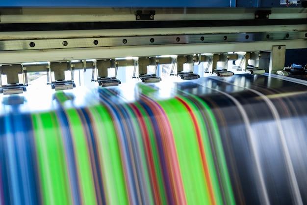 Mehrfarbiger großer tintenstrahldrucker, der auf vinylbanner arbeitet Premium Fotos
