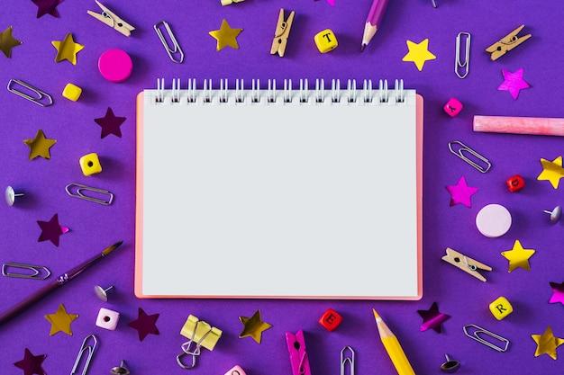 Mehrfarbiger schulbedarf auf violettem hintergrund mit kopienraum. Premium Fotos