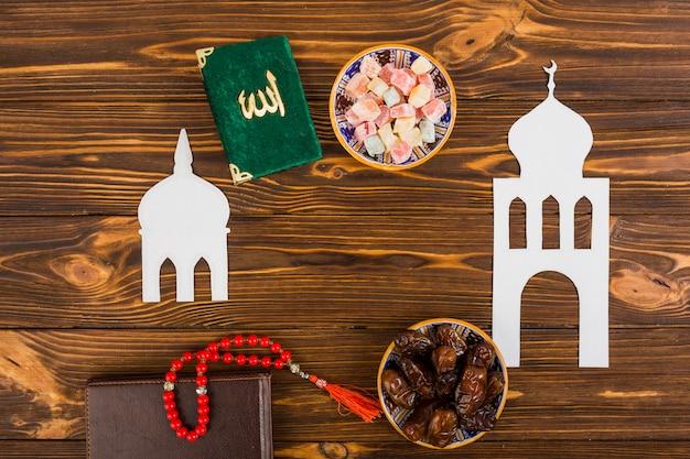 Mehrfarbiges lukum; kuran-buch; gebetsperlen und tagebuch mit ausgeschnittenen weißen islamischen moschee auf schreibtisch aus holz Kostenlose Fotos
