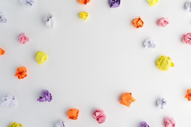 Mehrfarbiges zerknittertes papier vereinbart im kreisrahmen auf weißem hintergrund Kostenlose Fotos