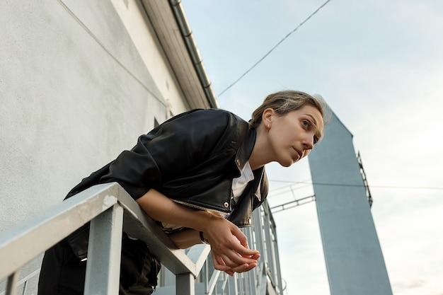 Melancholische einsame junge frau in der schwarzen lederjacke, die auf treppe mit wand auf hintergrund aufwirft. einsamkeit. Premium Fotos