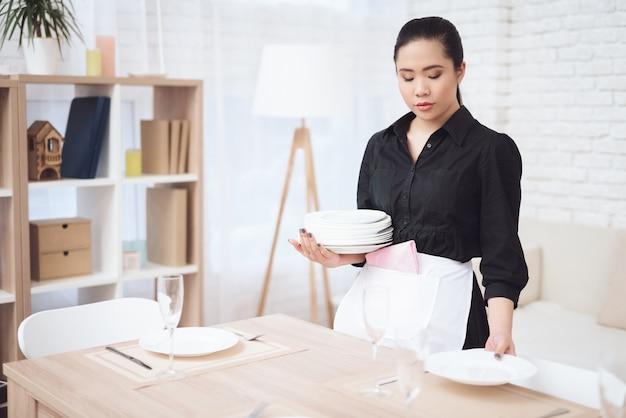 Melancholische haushälterin deckt tisch im hotelzimmer Premium Fotos