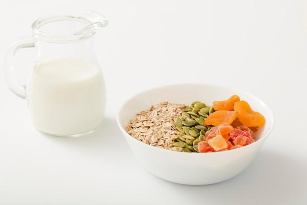 Melken sie mit gesunder schüssel muesli, kürbiskernen und trockenen früchten in der weißen schüssel auf weißem hintergrund Kostenlose Fotos