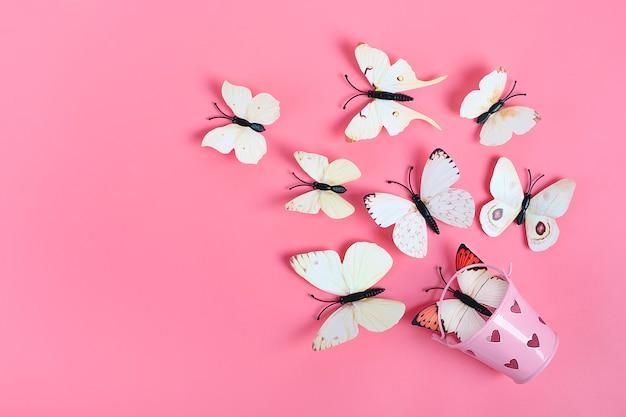 Menge der kohlschmetterlinge fliegen heraus vom eimer mit herzen auf rosa hintergrund Premium Fotos